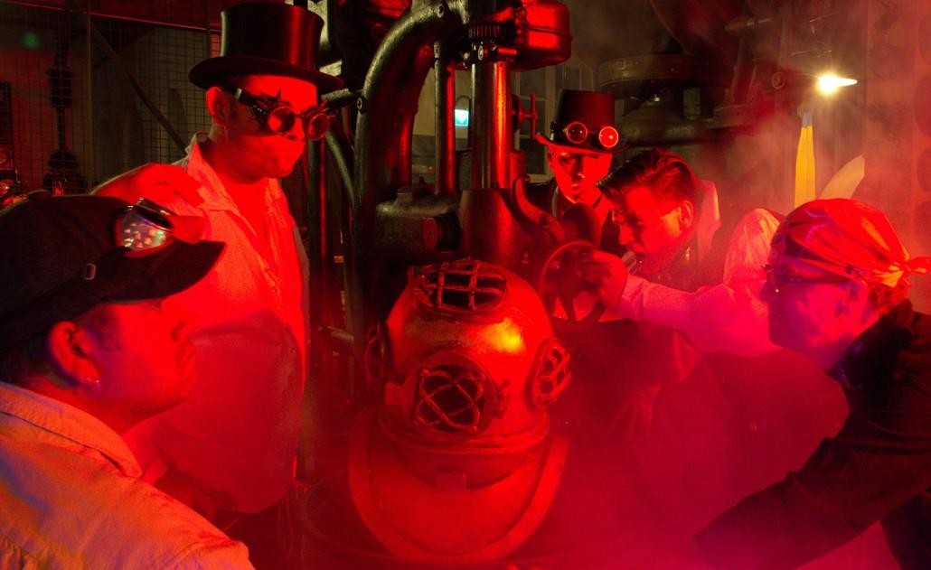 Covernaut am Periskop bei Rotlicht. Tauchhelm im Vordergrund